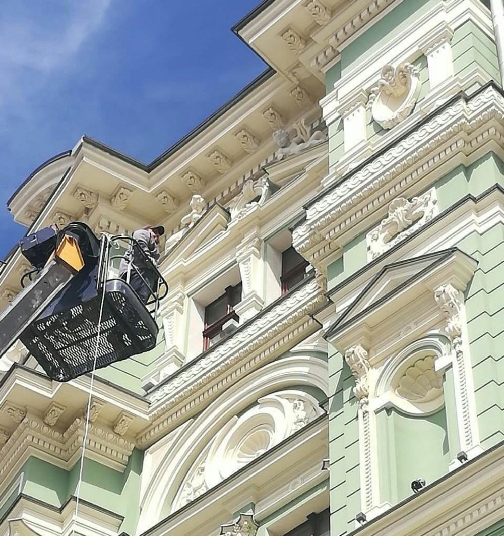 Рабочие восстанавливают скульптуру на фасаде Дома Руссова